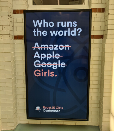 A sign from the ReactJS Girls Conference, reading 'Who rules the world?', with Amazon, Apple, and Google crossed out and replaced with the word 'Girls'